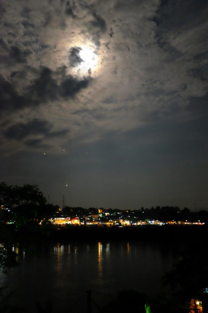 Looking across the Mekong to Laos in the moonlight. The small lights in the sky are paper lanterns.