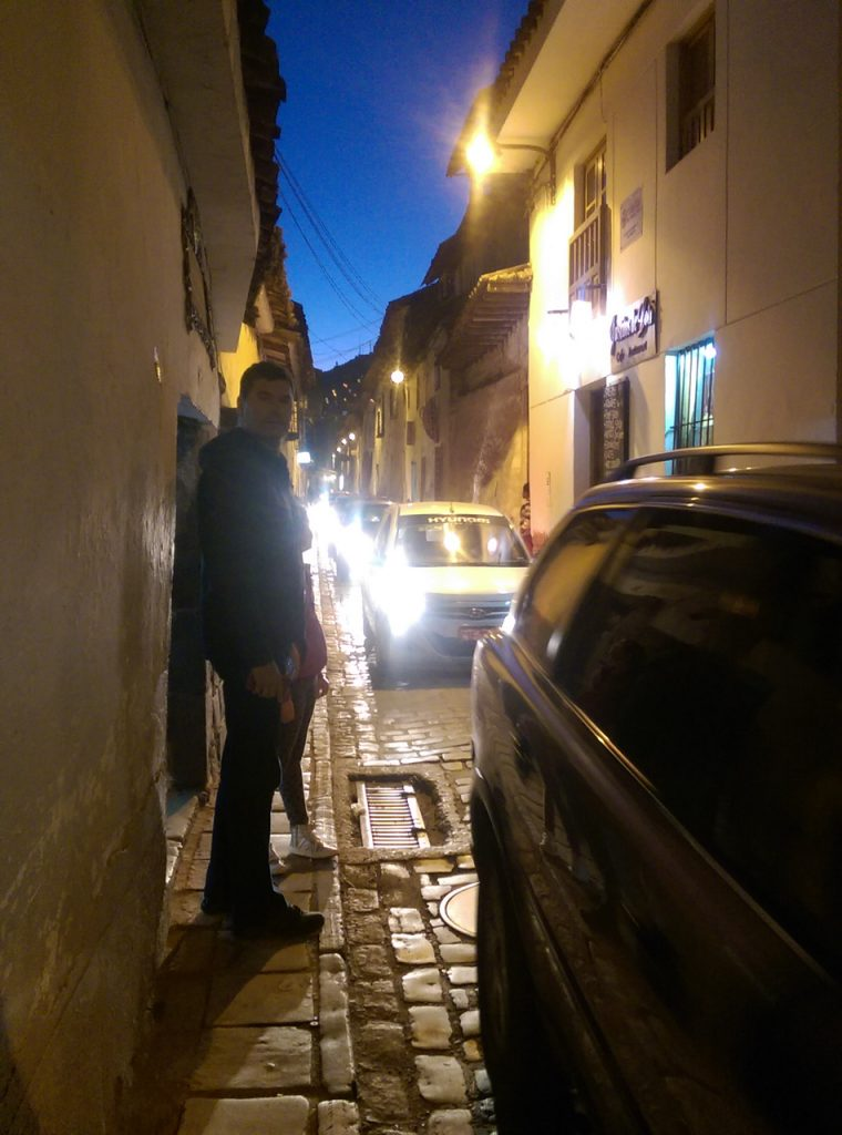 Narrow sidewalks and endless traffic in Cusco.