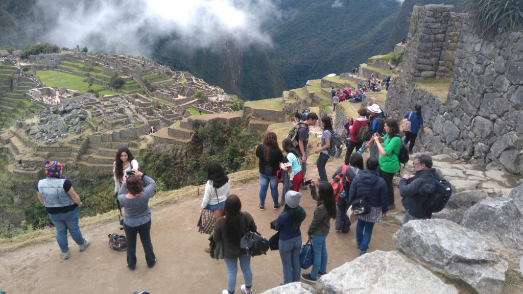 Tourists snapping photos with Machu Picchu in the background